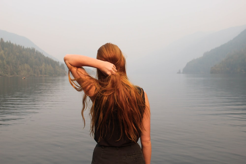 woman holding hair facing body of water during daytime