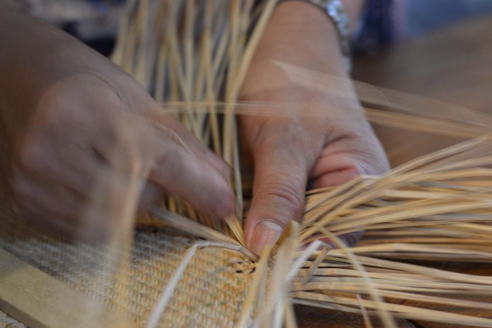 person woving beige straw