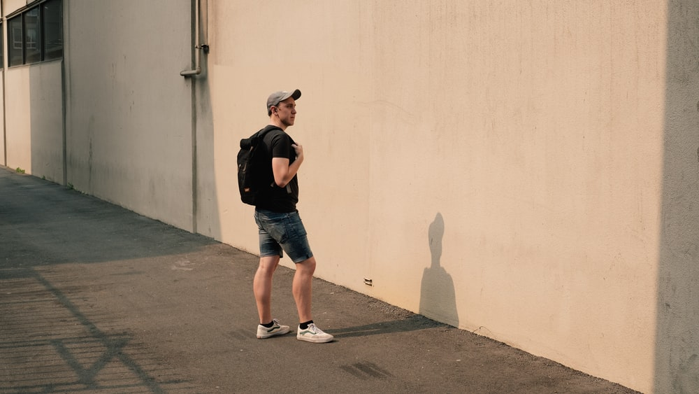 man standing beside white concrete wall
