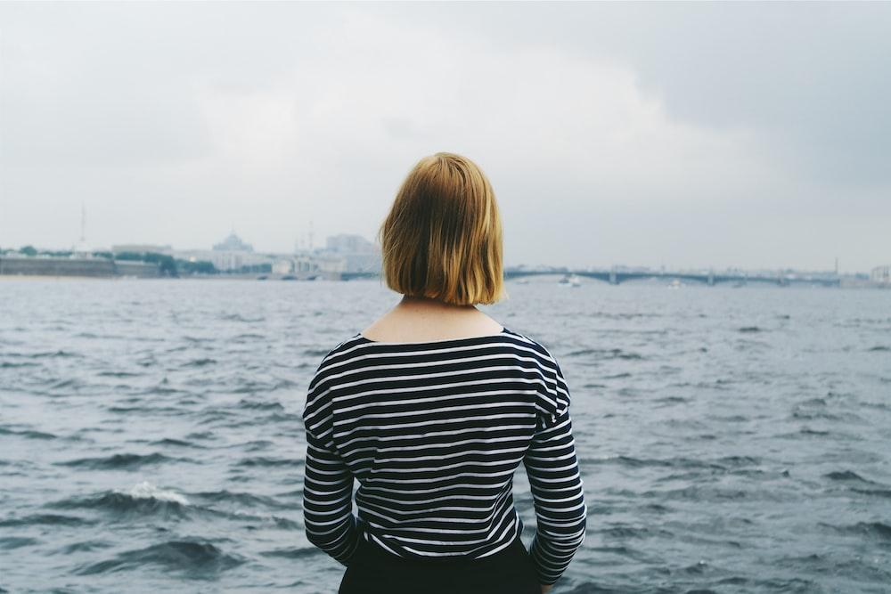 woman facing body of water
