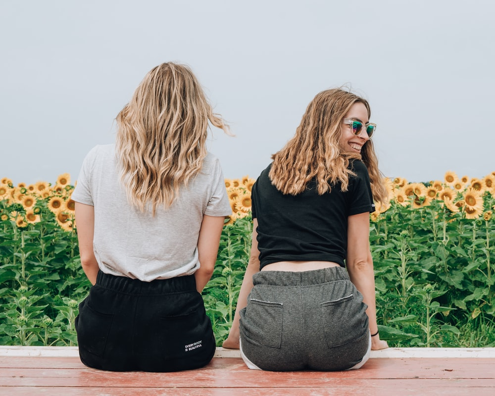 two women's sitting in front of sunflowers