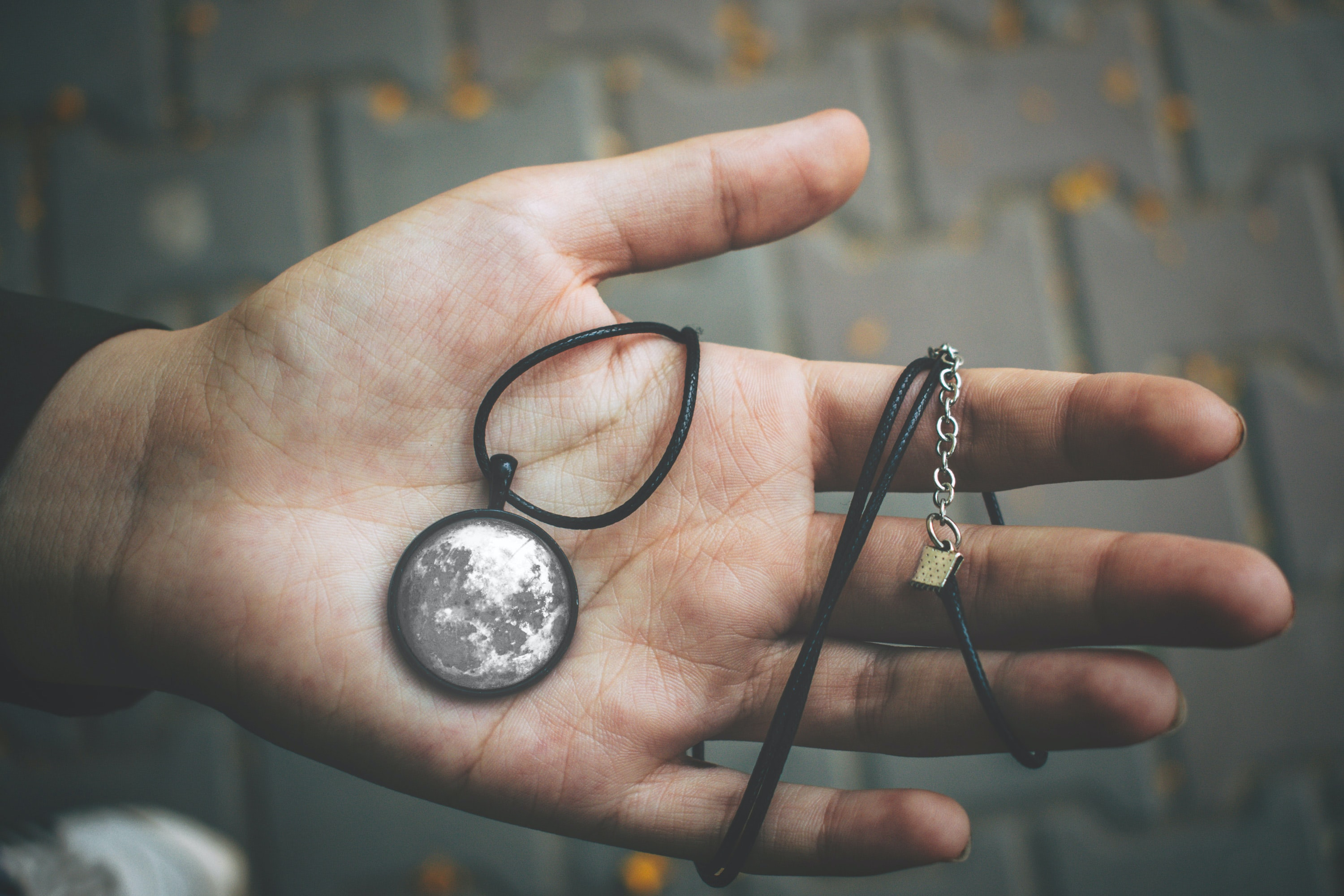 person holding moon themed pendant necklace