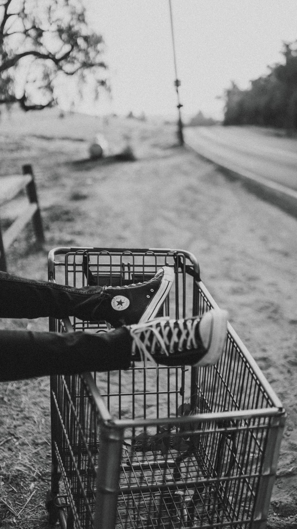 grayscale photo of person foot on metal grocery cart