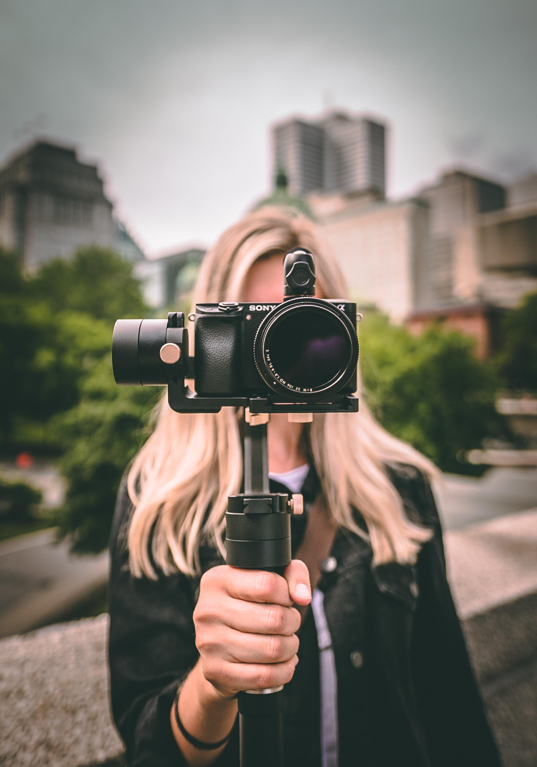 selective focus photography of woman holding camera gimbal