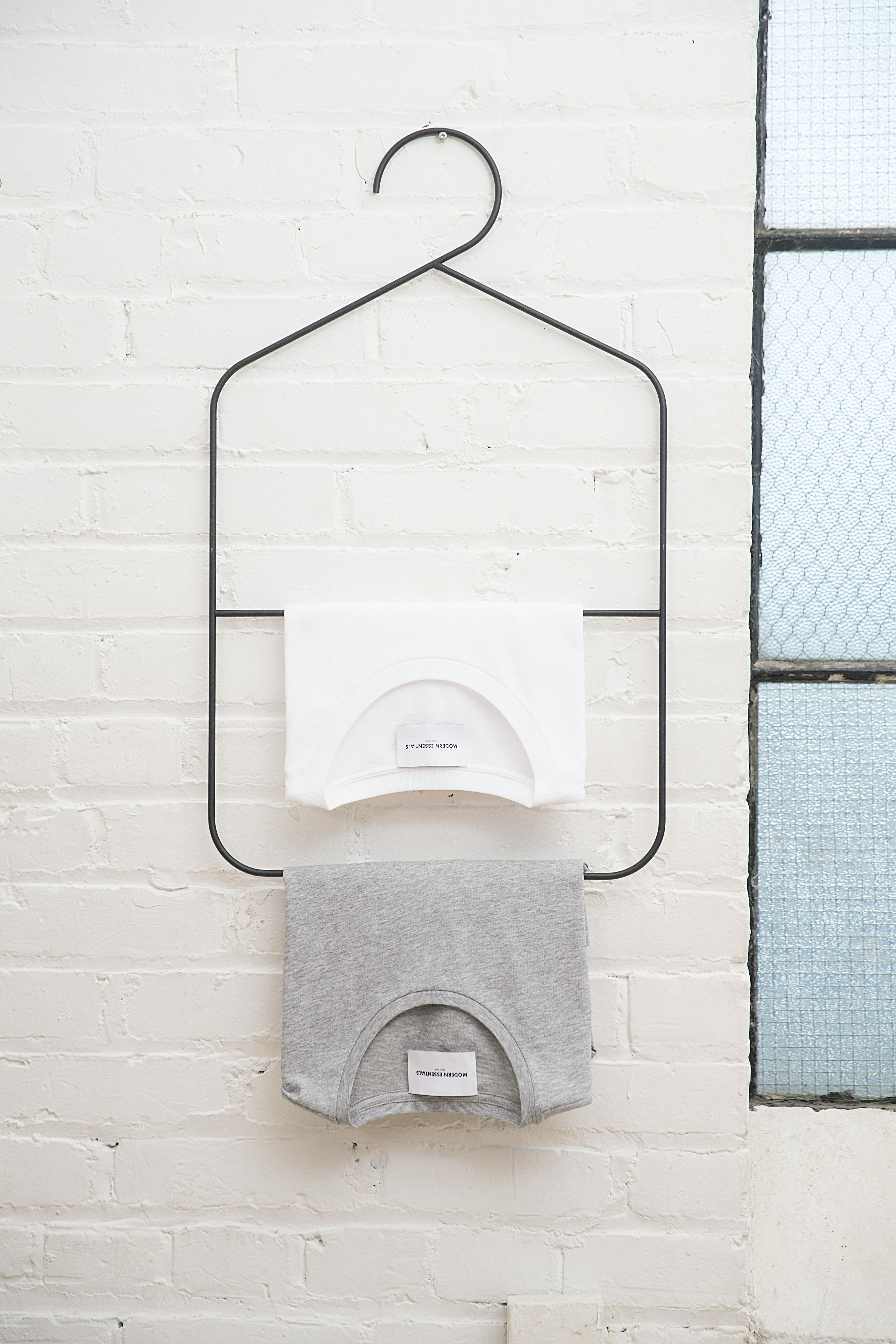 two white and heather gray shirts hanged on white wall
