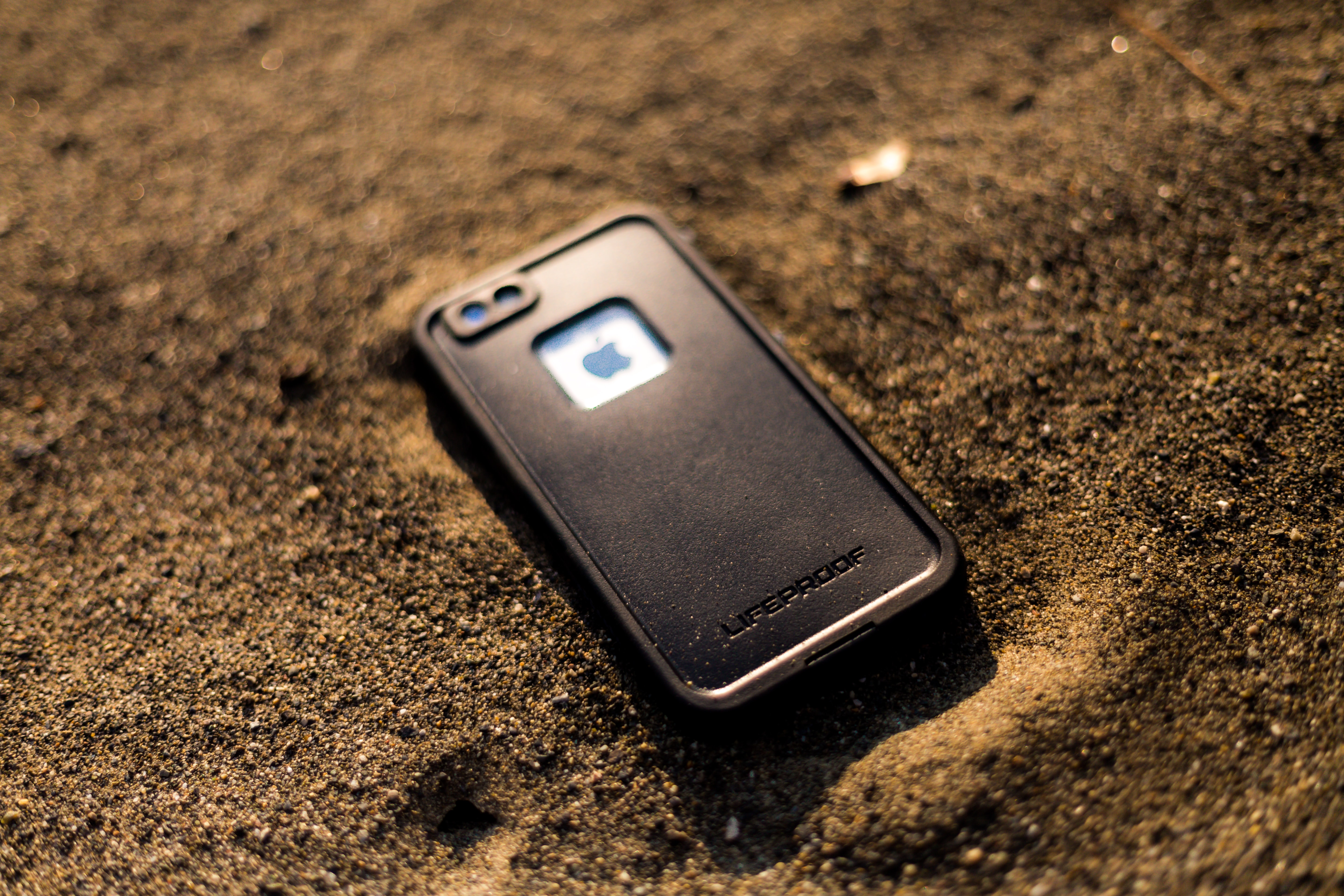 black Lifeproof iPhone case on brown soil