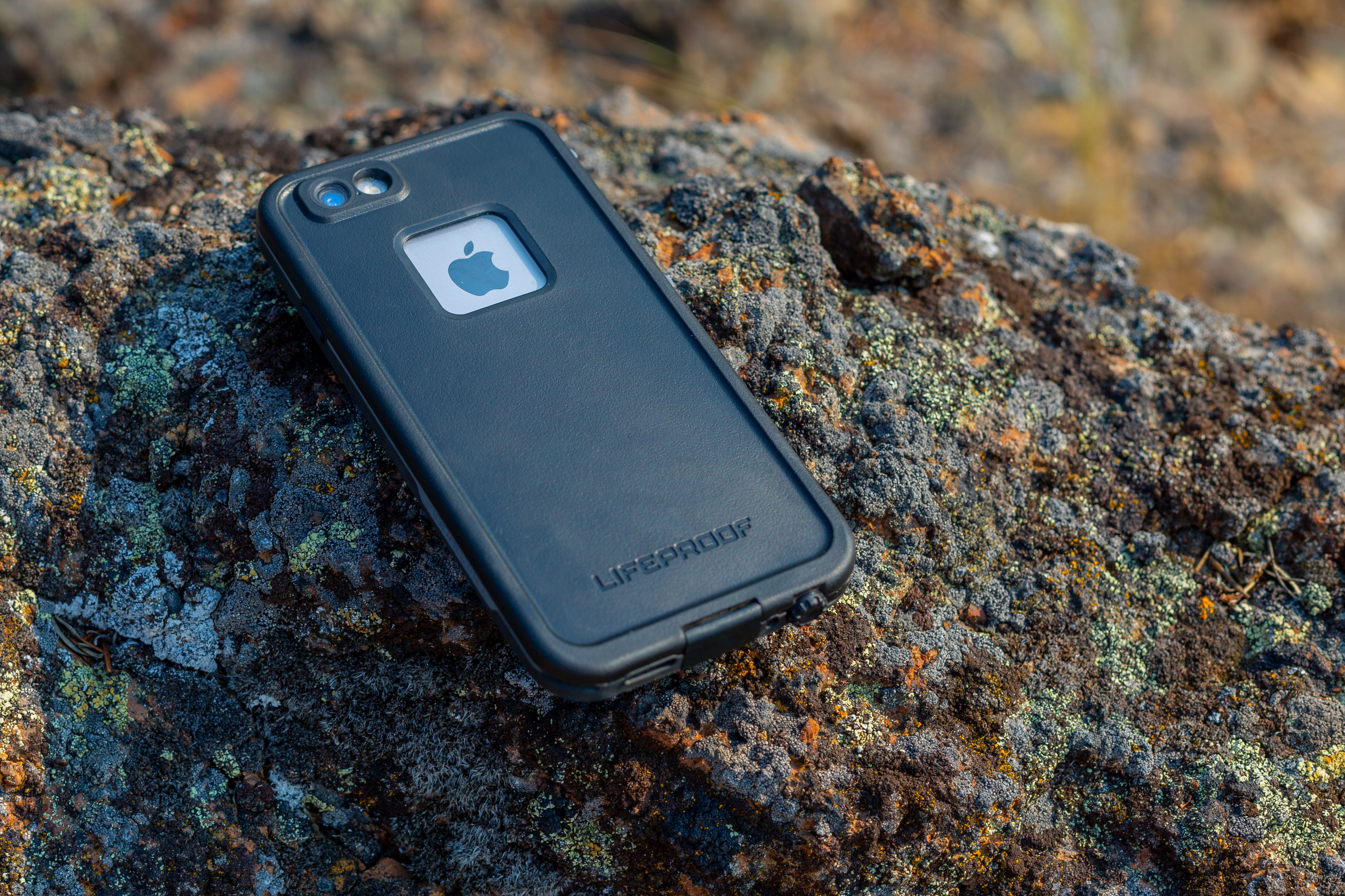 iPhone with black Lifeproof case on rock during daytime