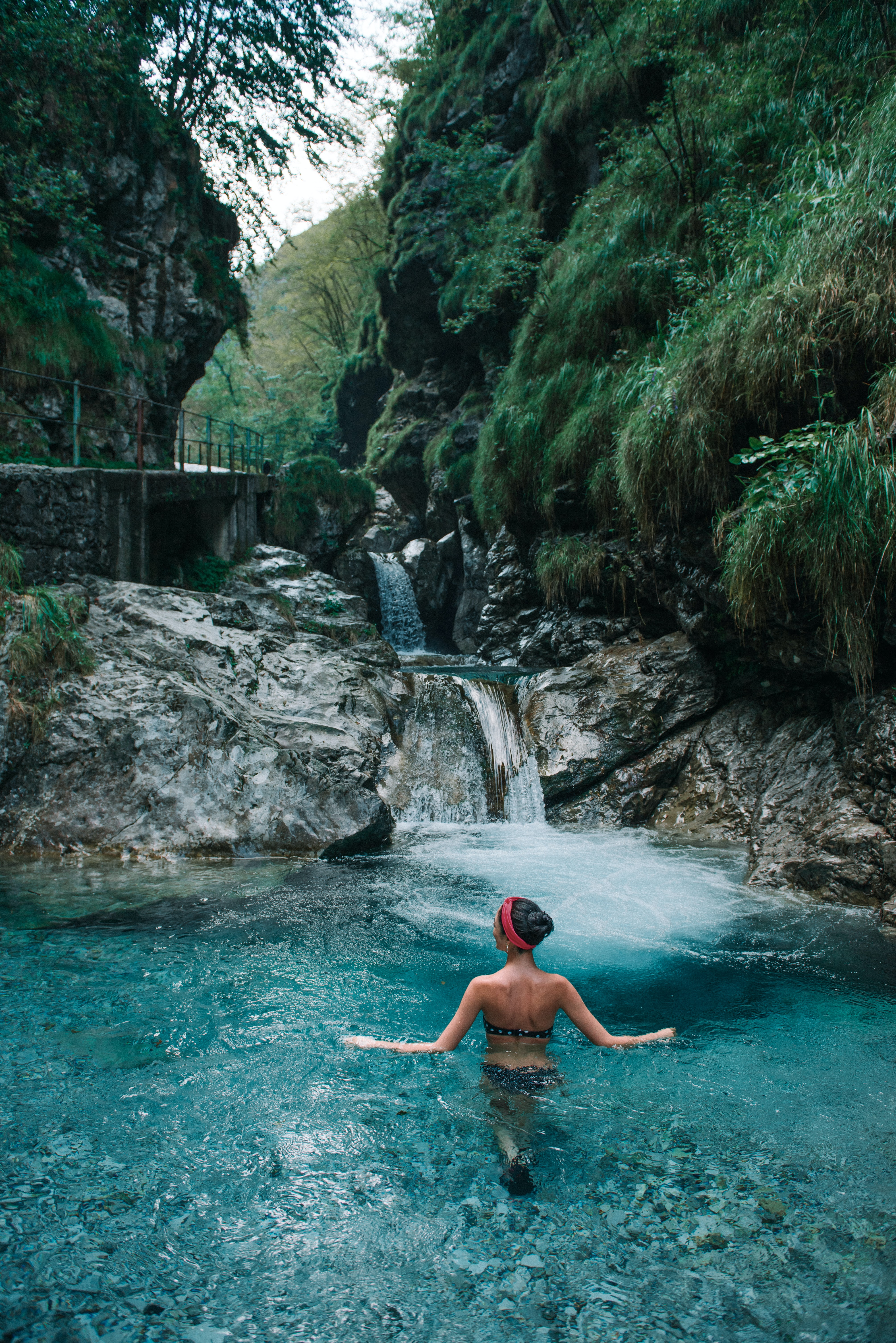 woman on body of water near waterfall during daytime