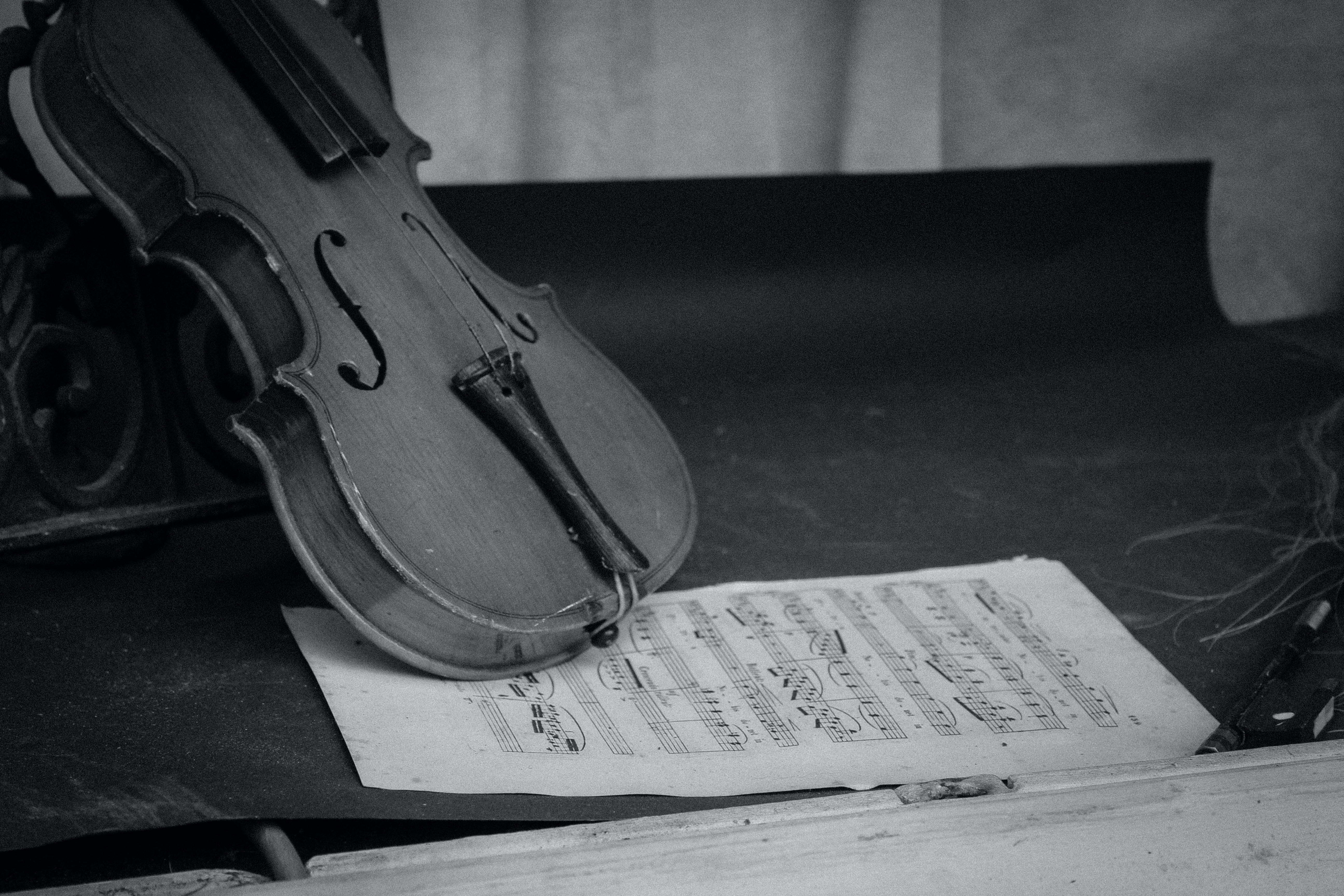 grayscale photography of violin on table with music sheet