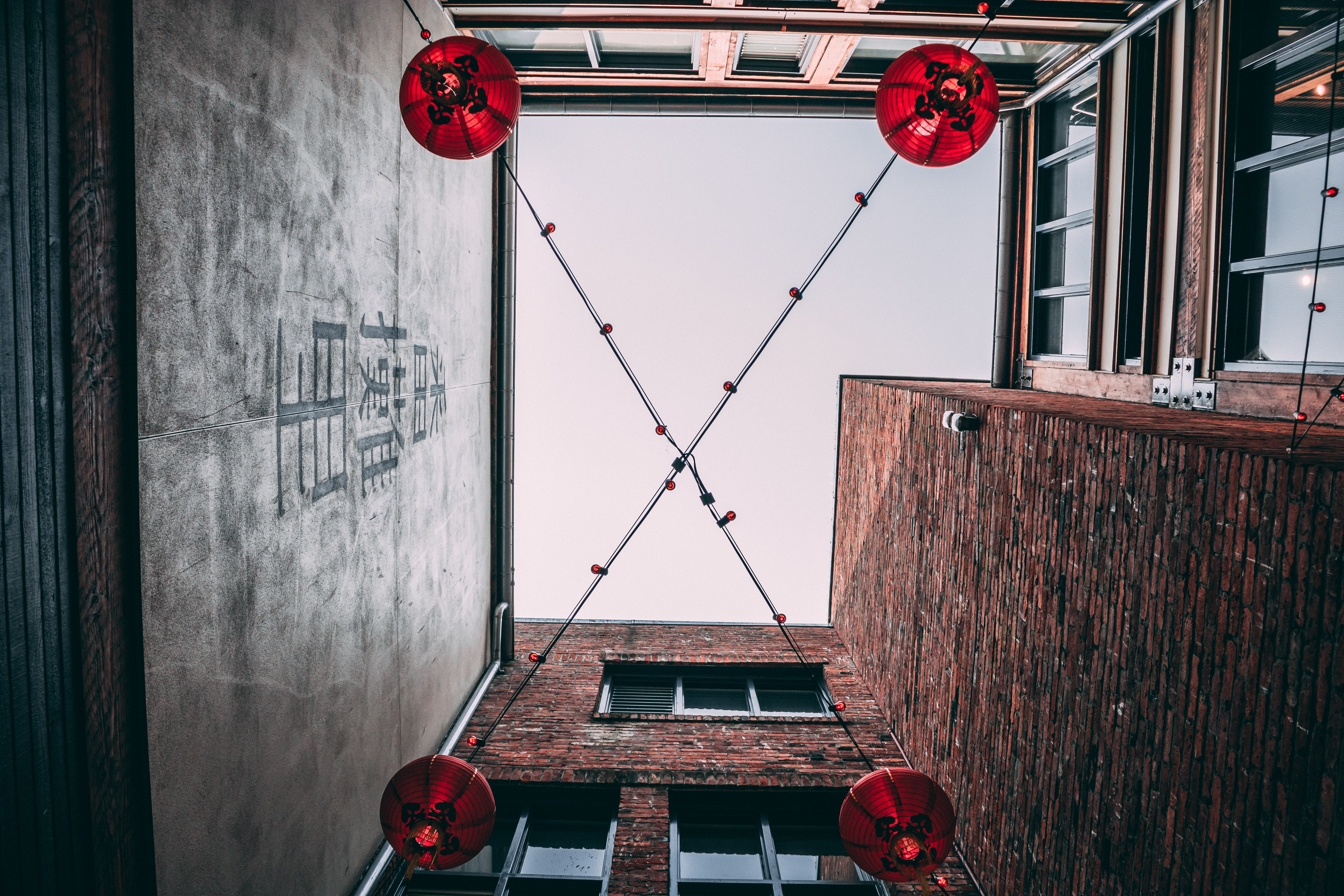four red paper lanterns near brown concrete building wall during daytime