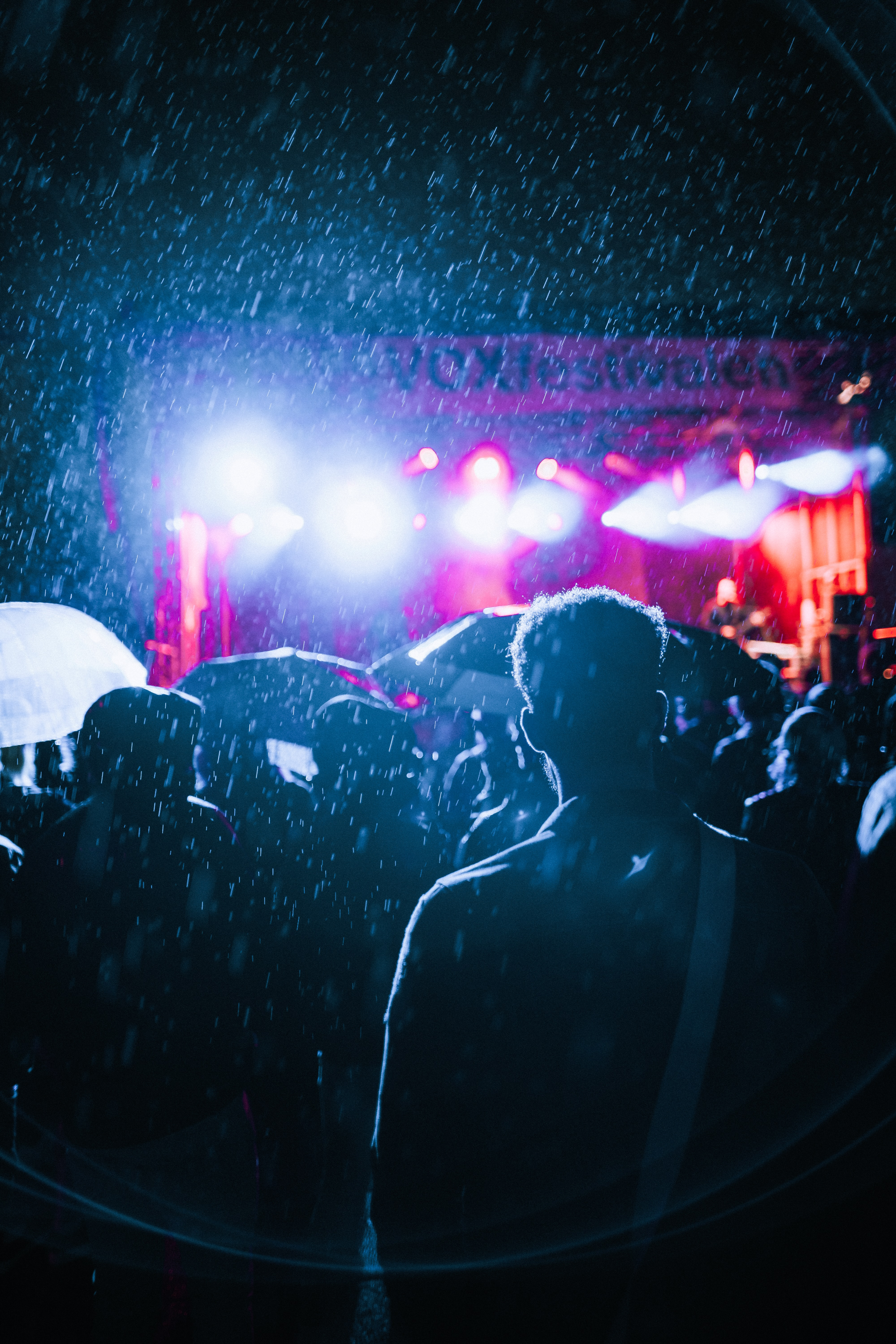 people watching live concert during rain