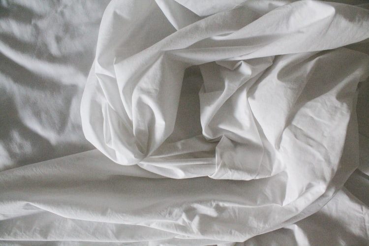 white bed sheet on a bed