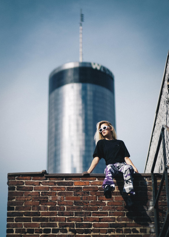 woman sitting on brick wall