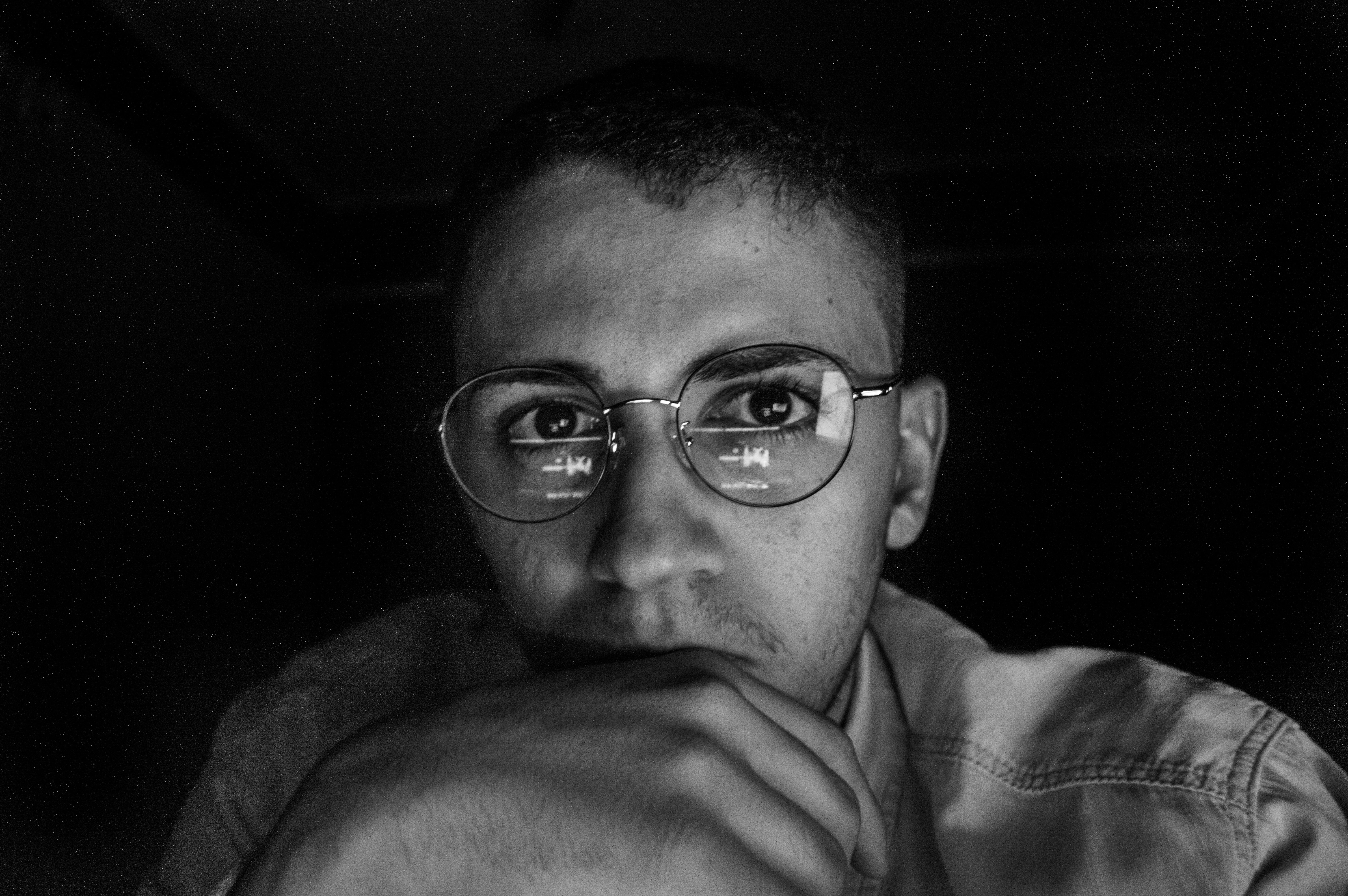 greyscale photo of man wearing eyeglasses
