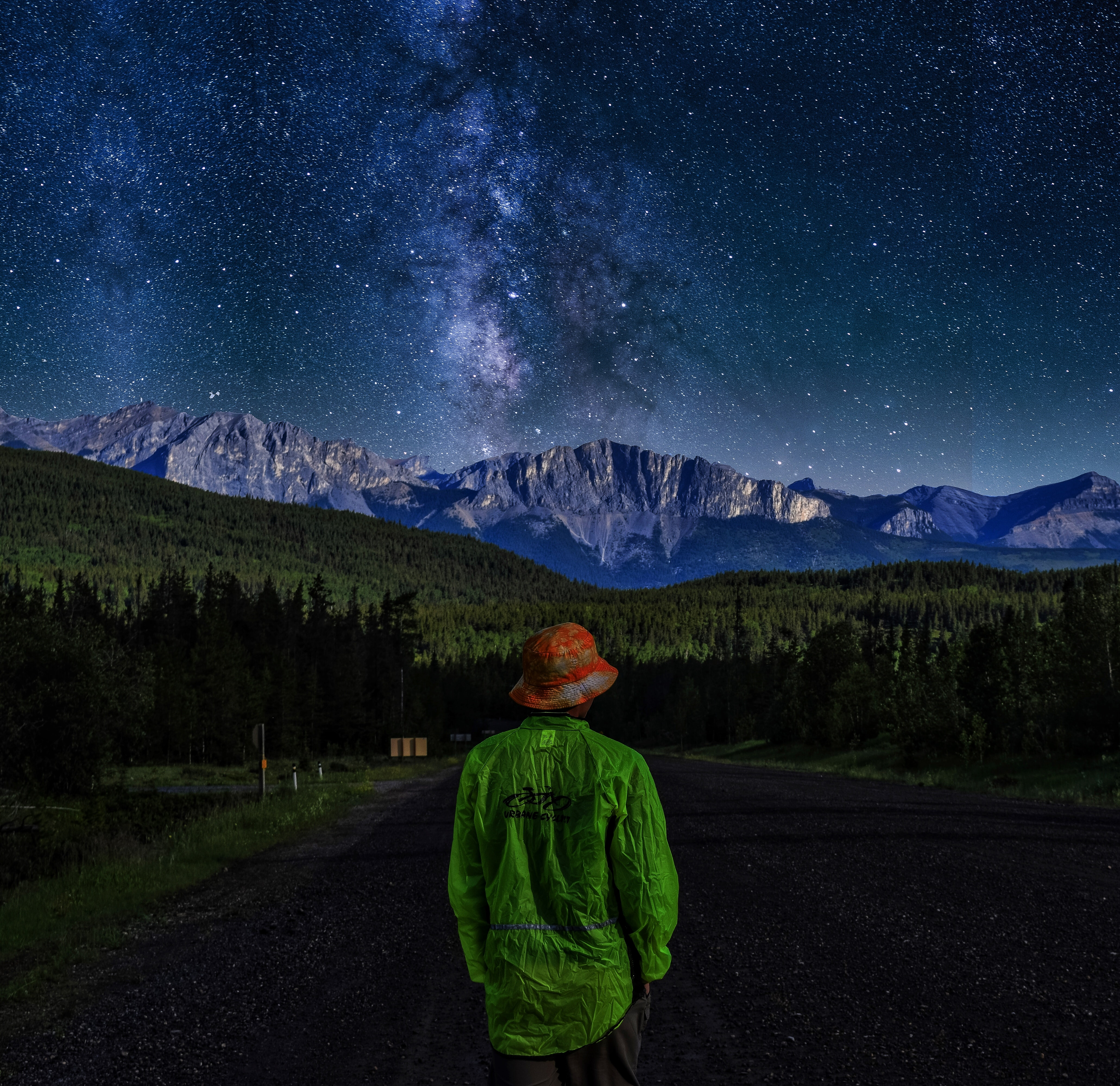 person wearing green sweater standing near the house during nighttime illustration