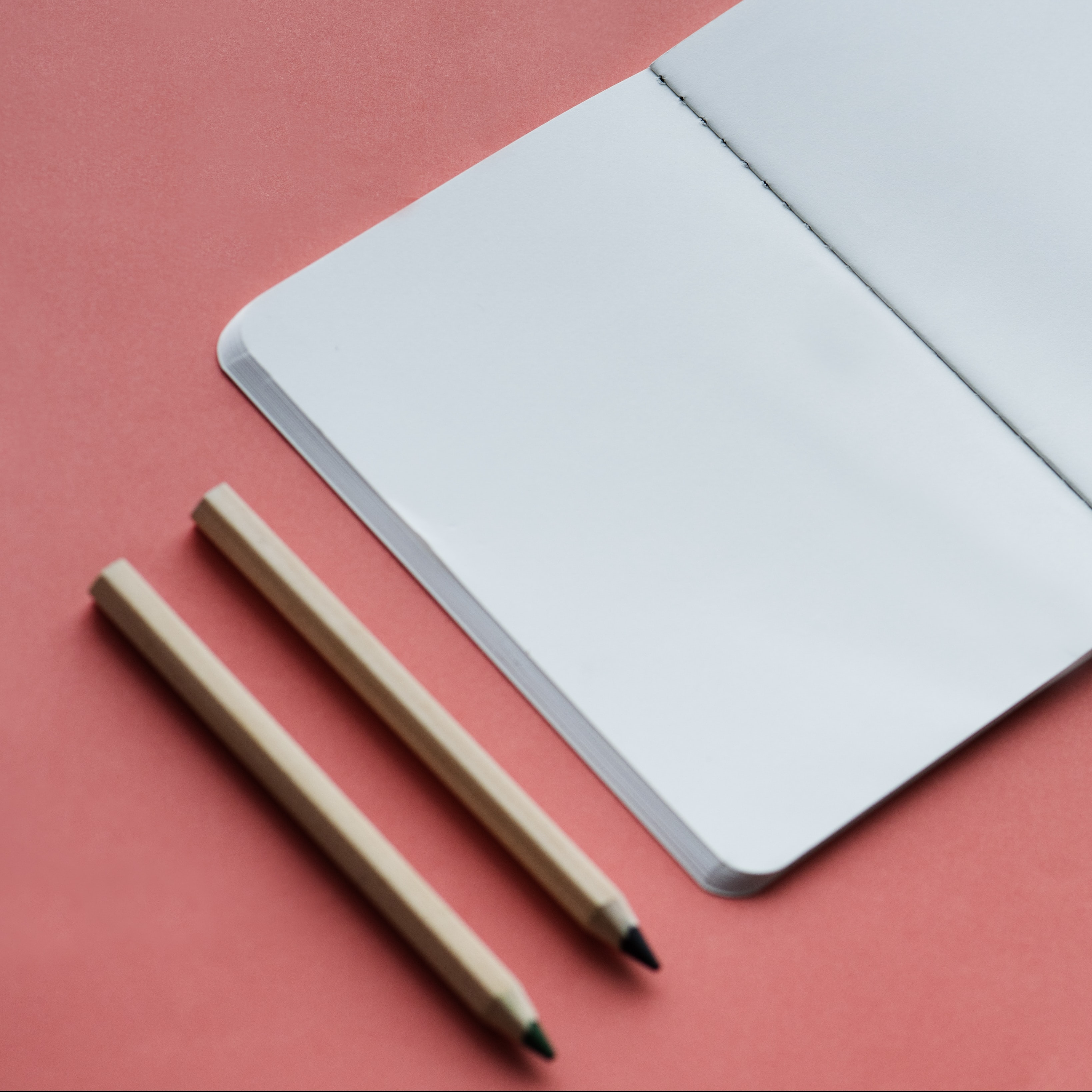 closeup photo of open book beside pencils
