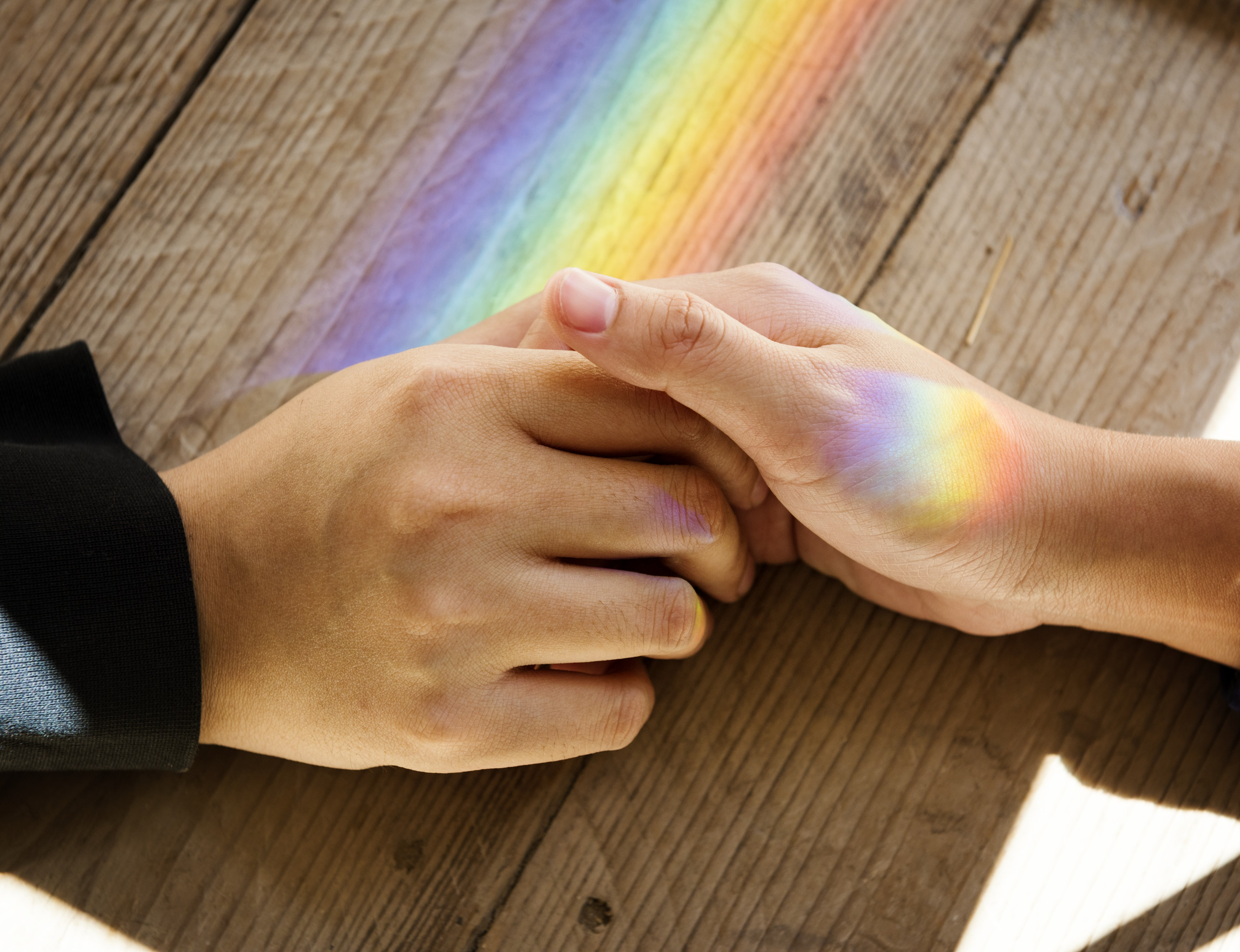 two holding hands on table with rainbow