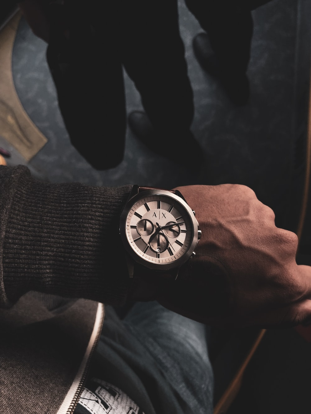 person wearing round gray chronograph watch