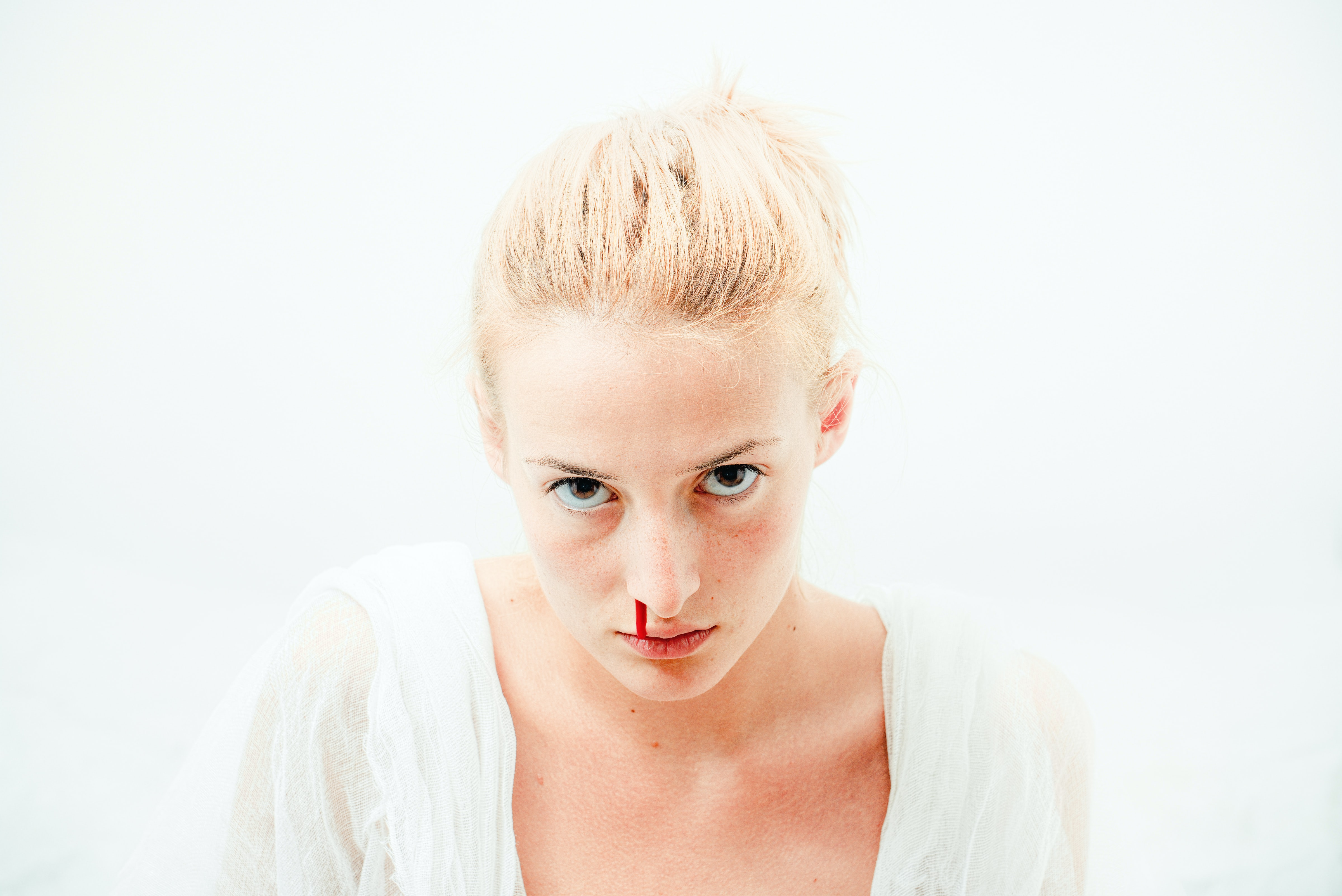 woman's bleeding nose with white background