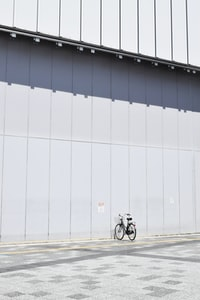 black commuter bike parking beside wall at daytime