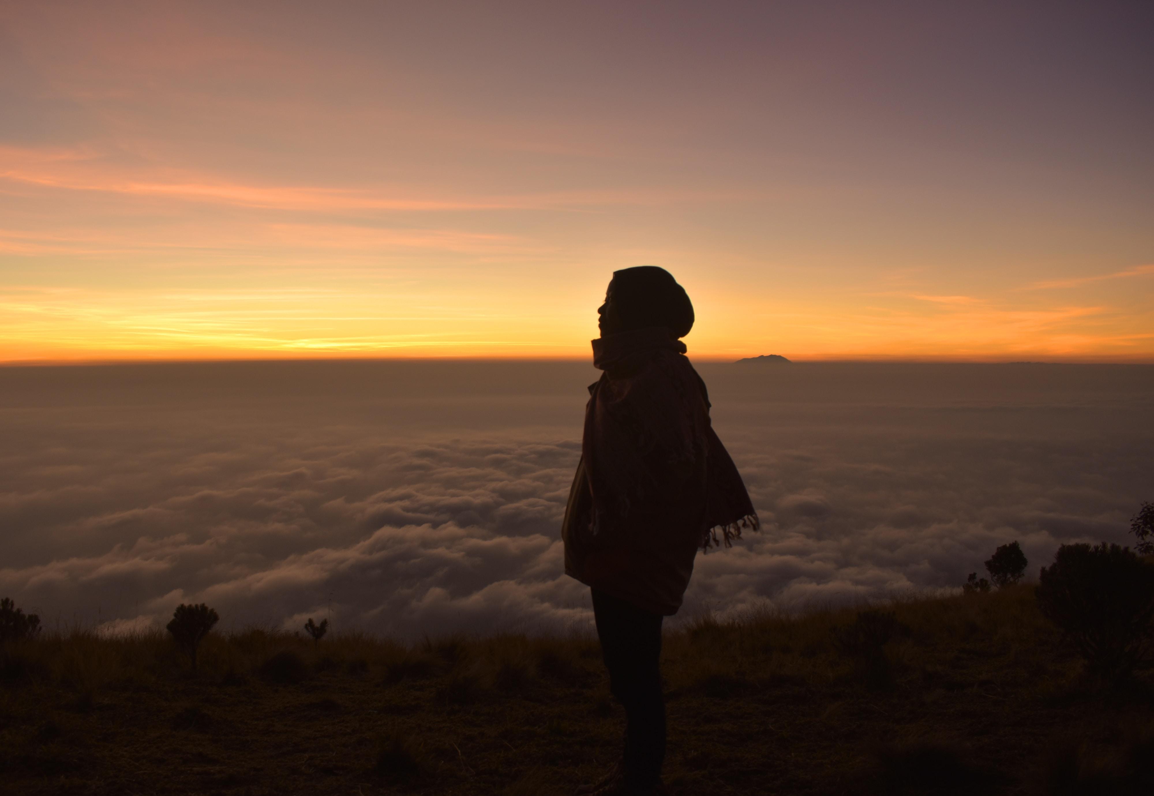 woman looking sideways standing near cliff