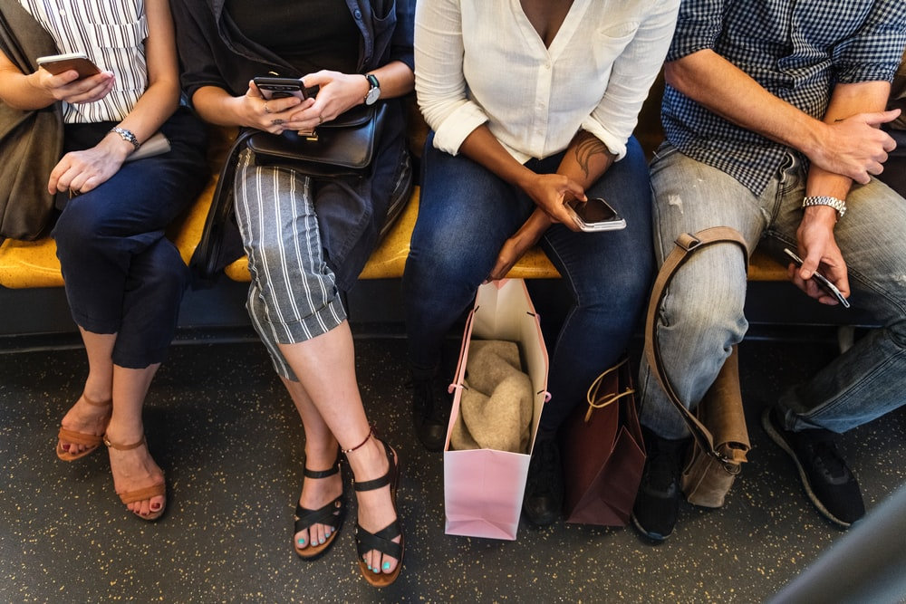 sitting people while holding their own smartphones