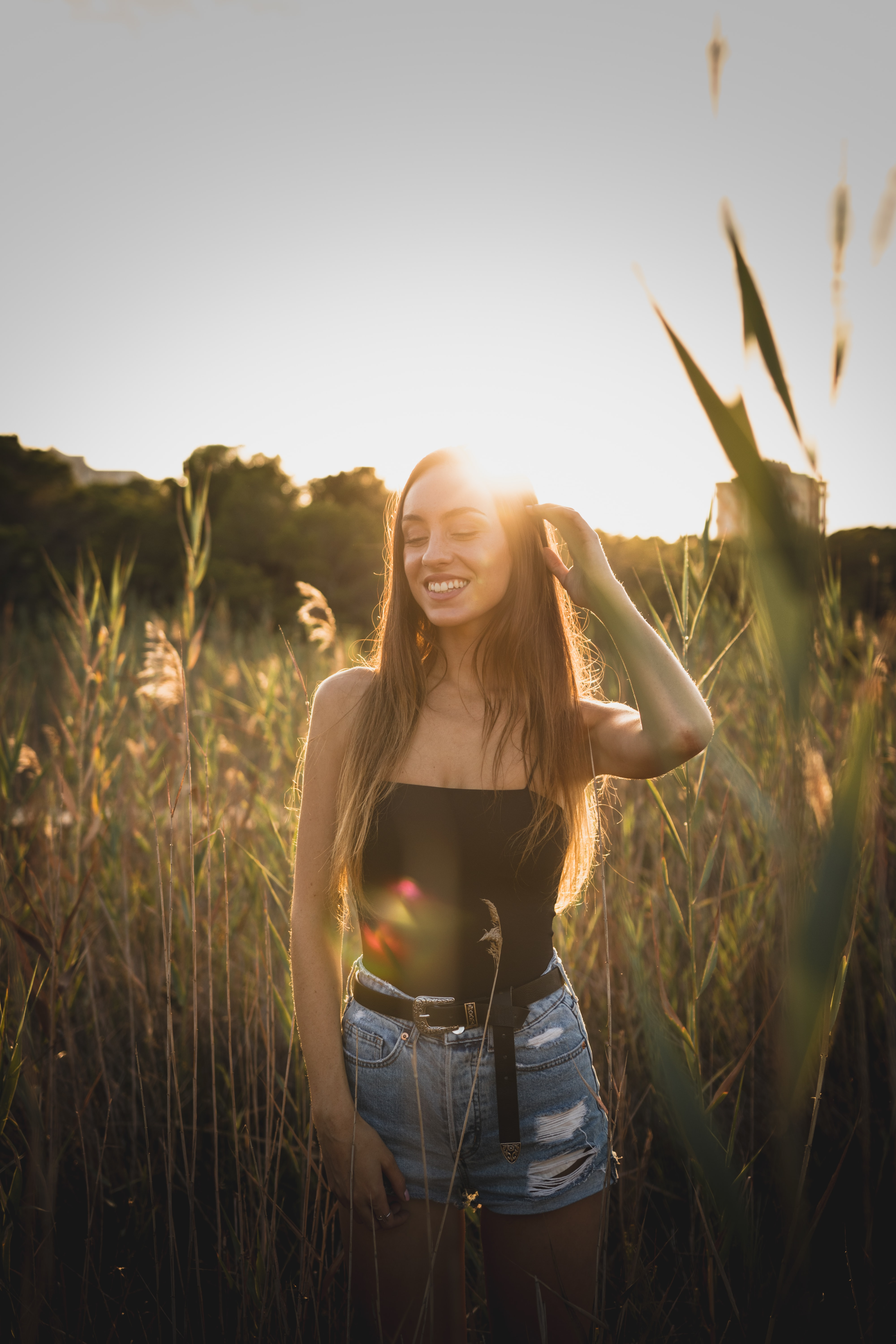 smiling woman in black strapless top and blue distressed shorts standing near green grass during sunset