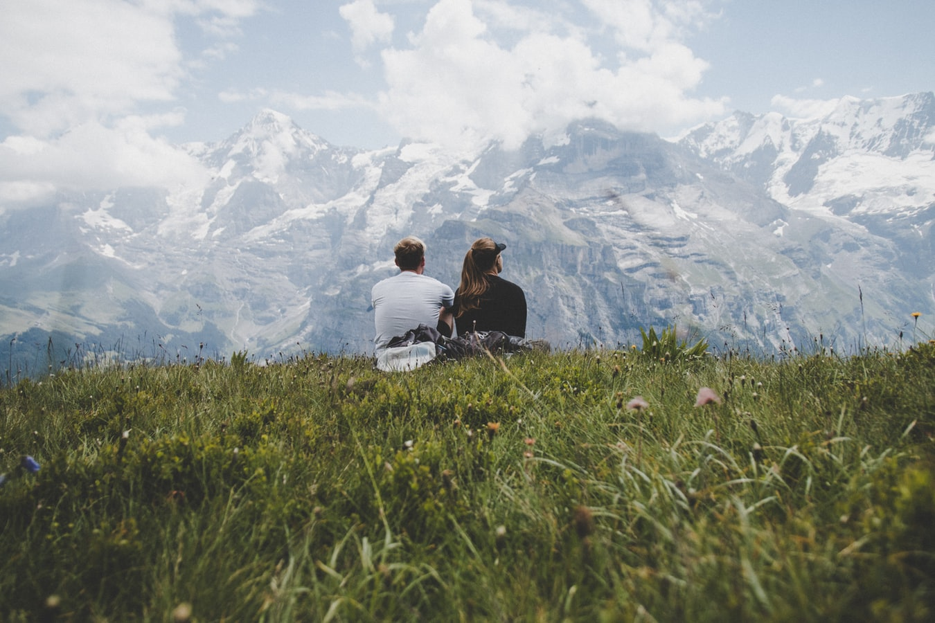Couple sitting near a snow capped mountain range, discussing their marital problems