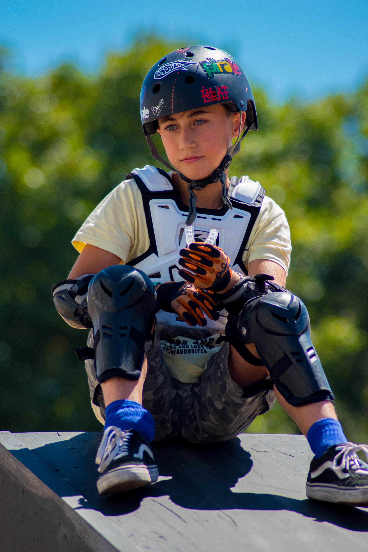 boy in bicycle helmet sitting on gray wooden platform