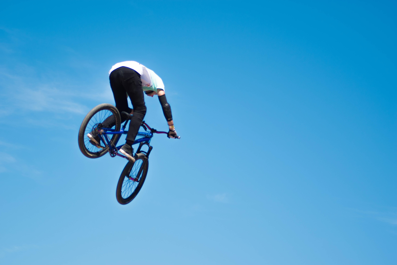 man ridding blue BMX bike