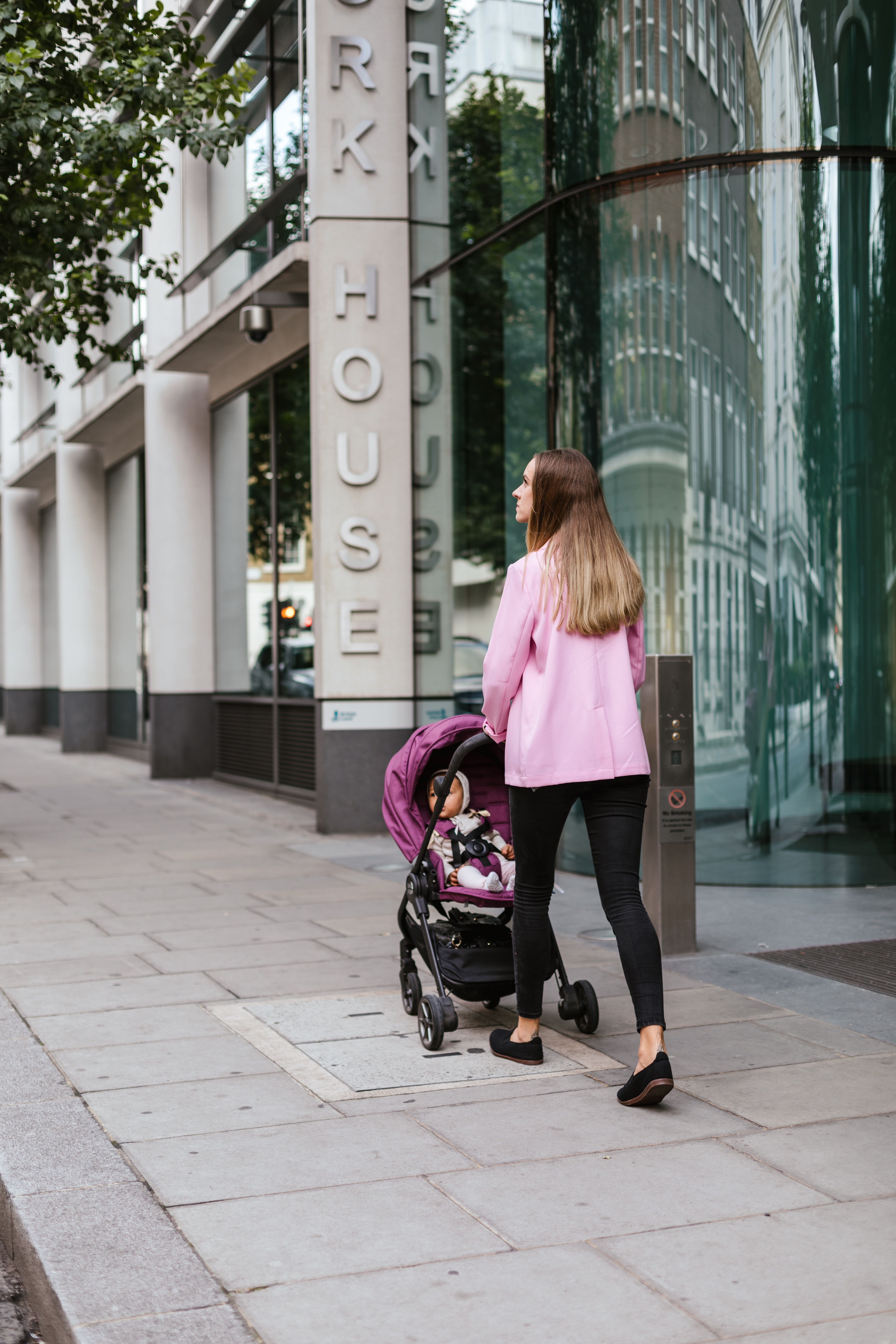 woman walking with child inside stroller