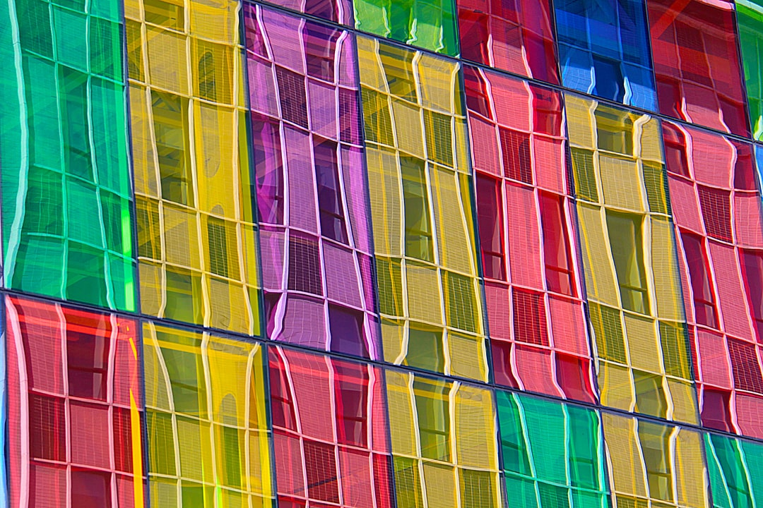 My wife and I were on vacation for the first time visiting Montreal and Toronto.  As we walked from the part classed as Old Montreal into the new part, we came across the Palais des Congres, which has these beautifully colourful windows.  Whatever the weather, this building would always put a smile on my face.