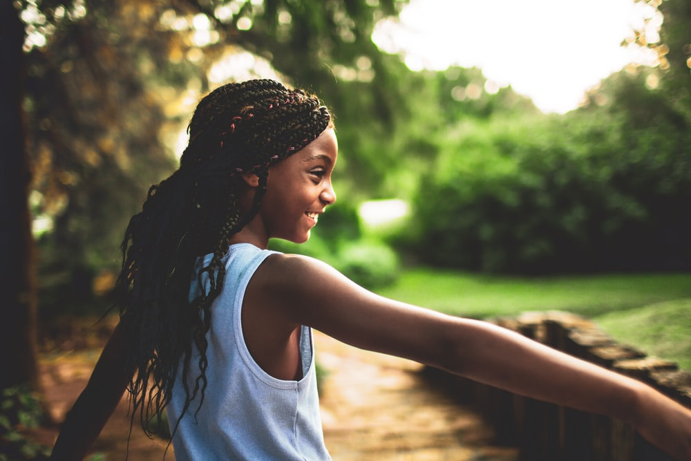 shallow focus photography of girl in white tank top near tree during daytime