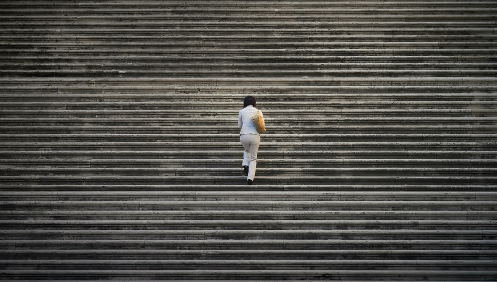 person in white suit walking on staircase