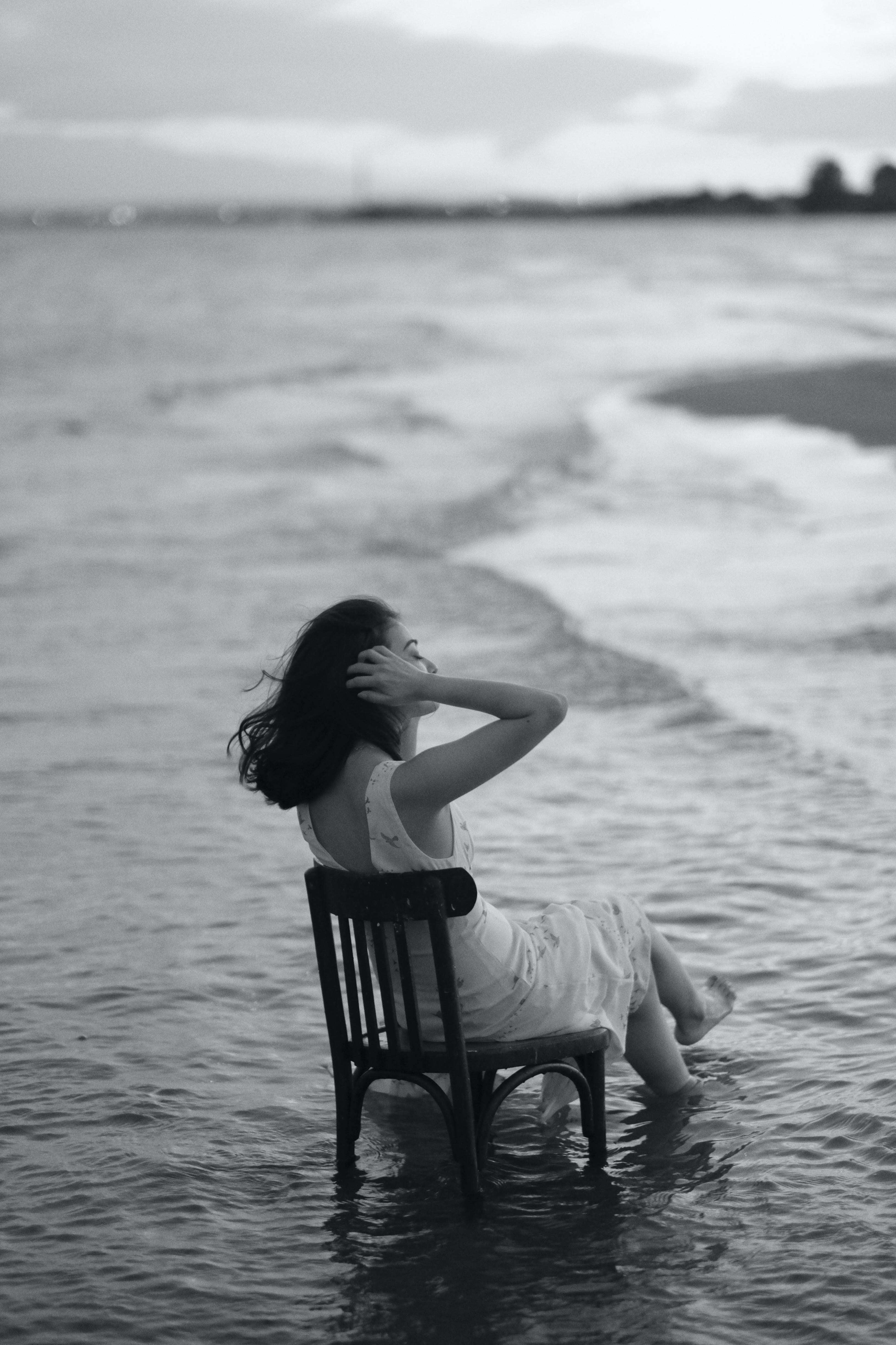 grayscale photography of woman sitting on chair on body of water