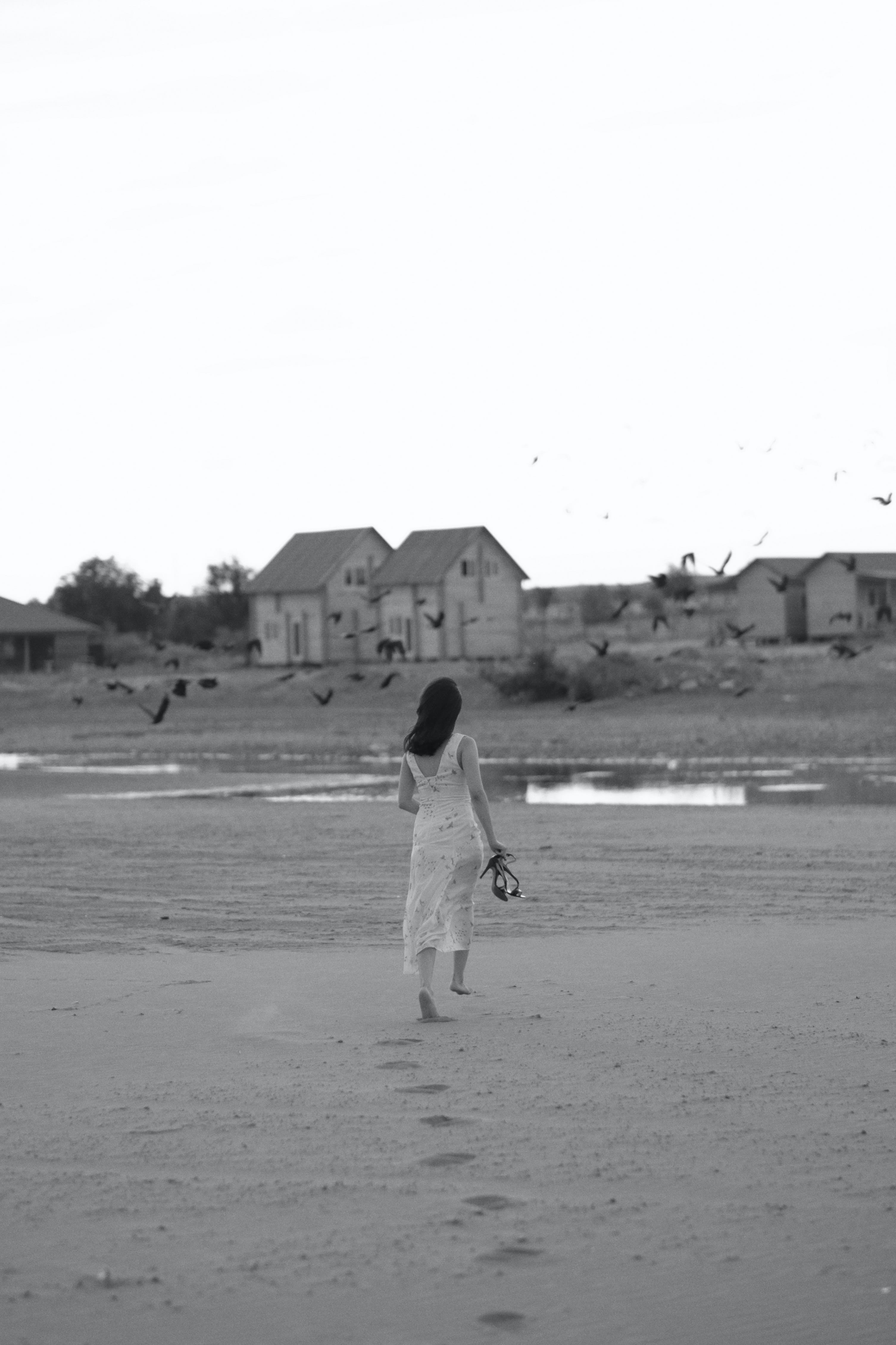grayscale photo of woman walking on sand