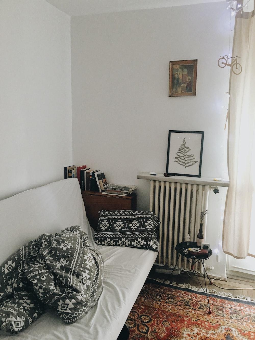 white sofa with throw pillows on wall