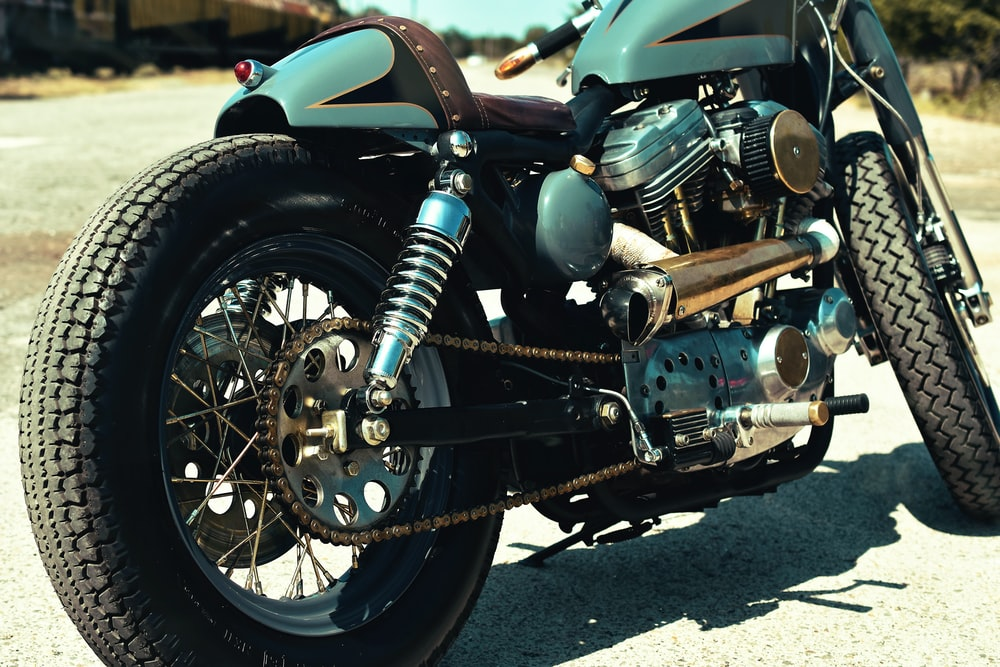 close-up photo of teal and black motorcycle