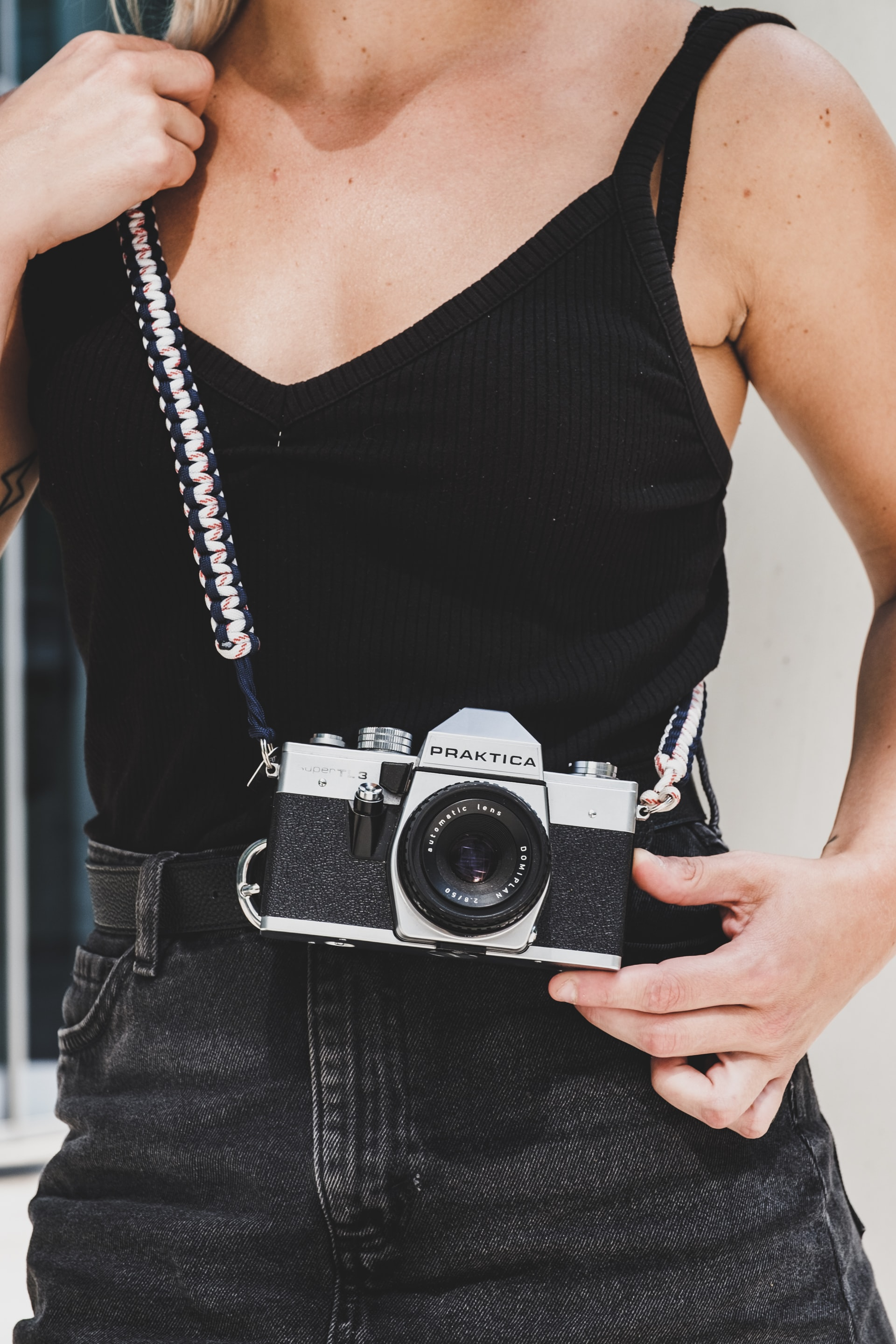 woman wearing black spaghetti strap camisole holding black and gray Praktica SLR camera