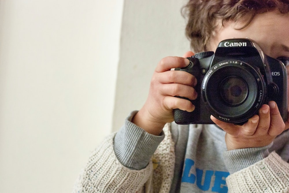 boy holding Canon DSLR camera