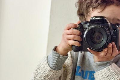boy holding canon dslr camera canon zoom background