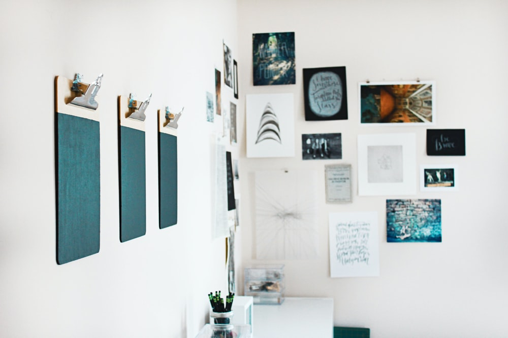three green clipboards on wall