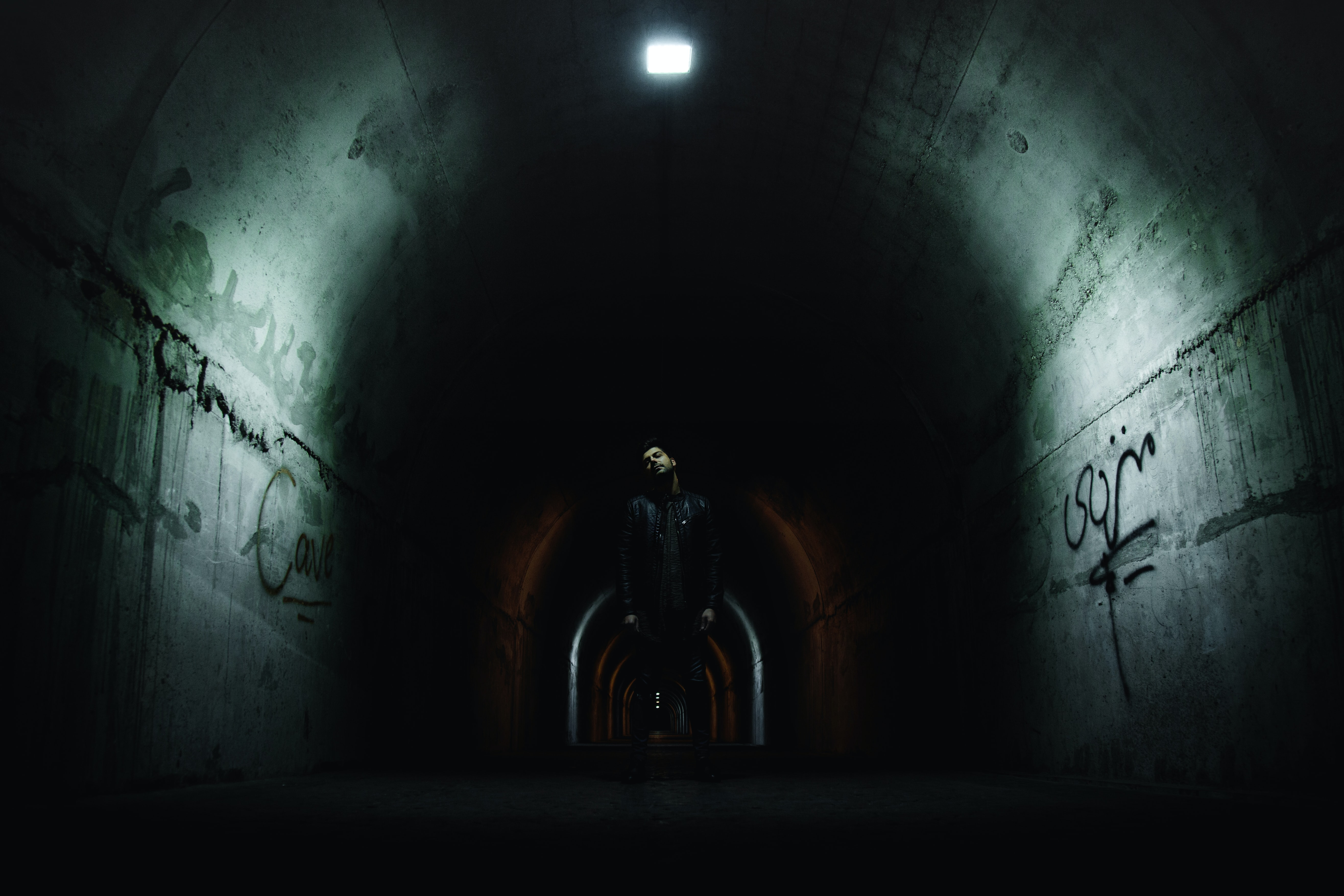 man standing in the middle of the tunnel under the light