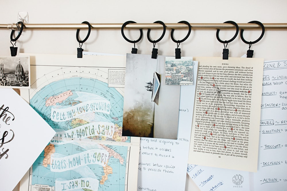 white printer papers hanging on brown metal rod