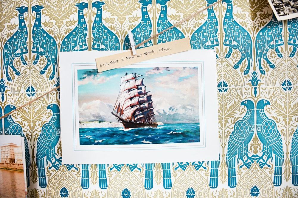 white and blue boat on body of water painting