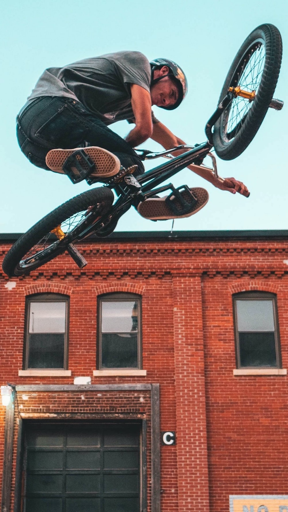 man riding on black BMX bike in mid-air