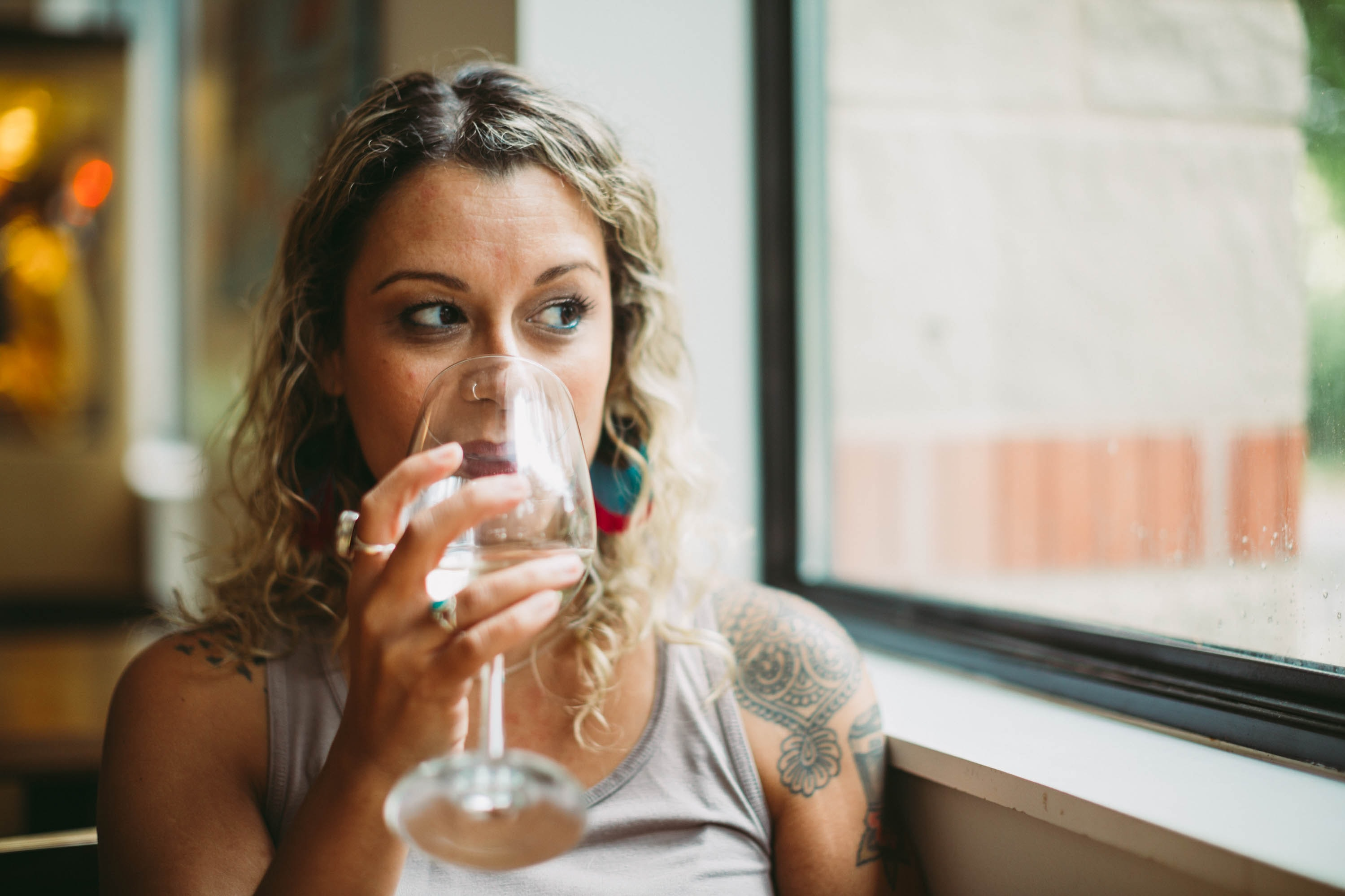 woman drinking using a wine glass beside a glass window at daytime
