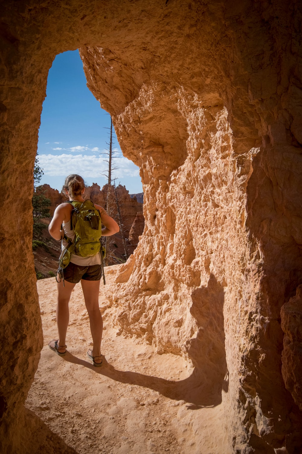 woman carrying backpack standing in cave passage