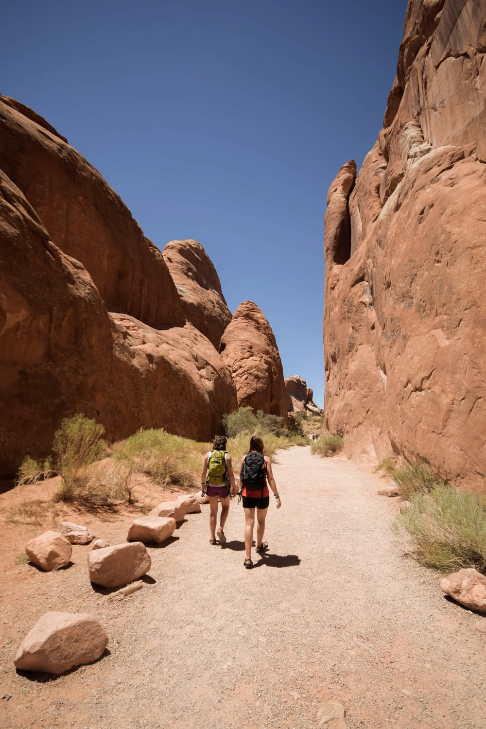two people walking along rock formations