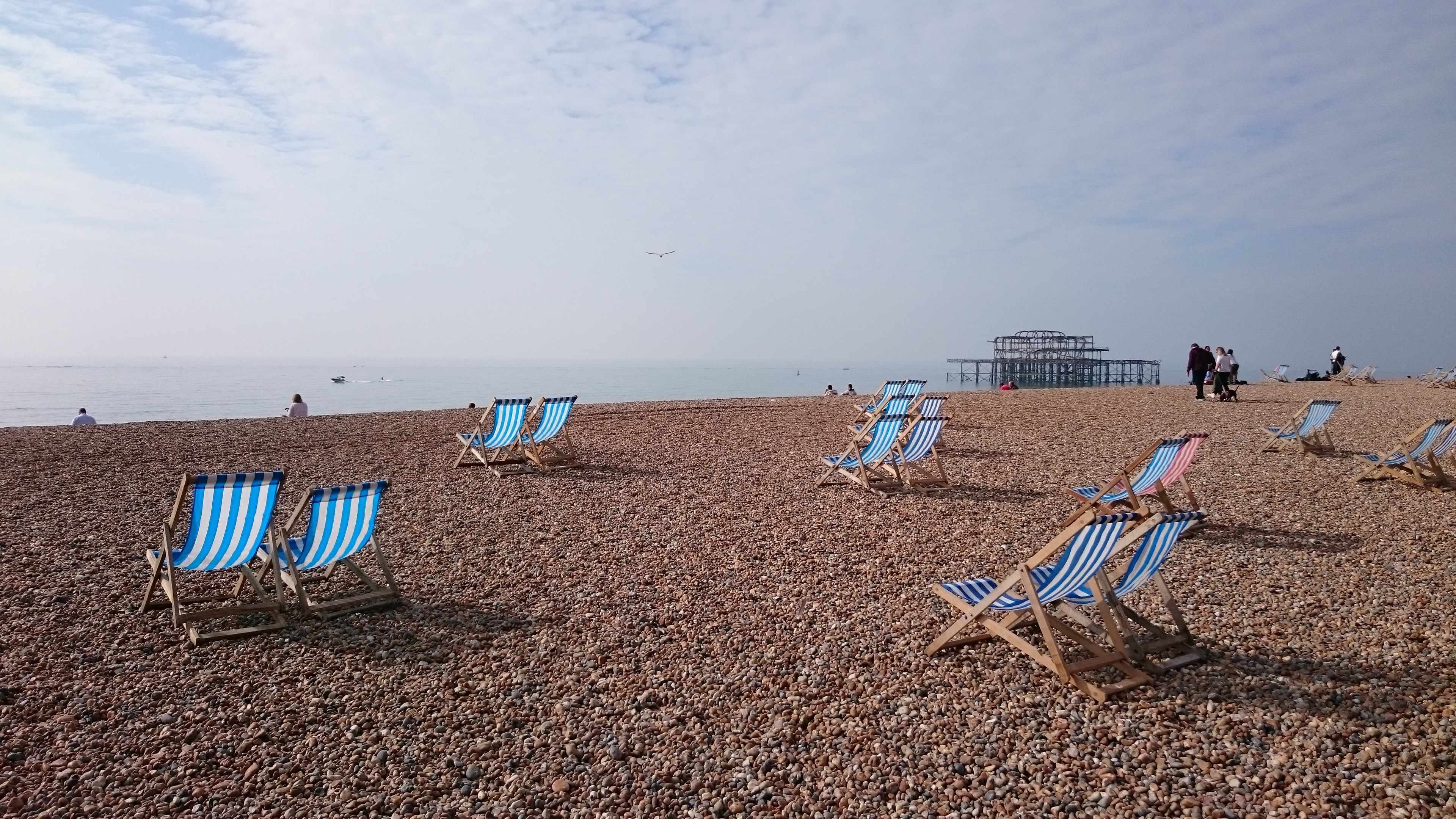 blue and white wooden chairs near seaside